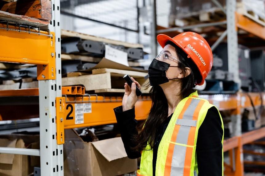 Katerine Ortiz inspecte un palettier dans un entrepôt.