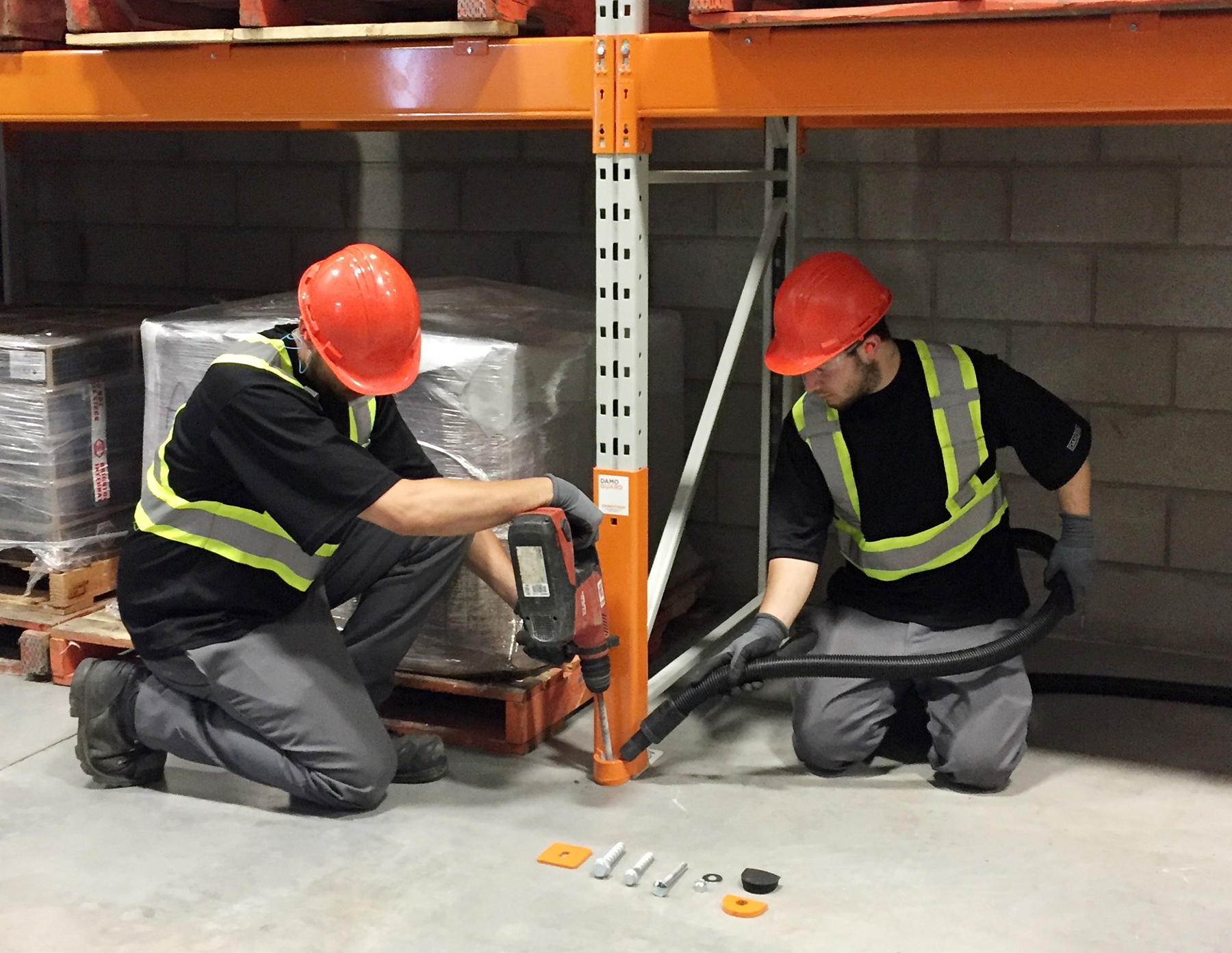 two men installing a Damo Guard to protect a pallet rack upright