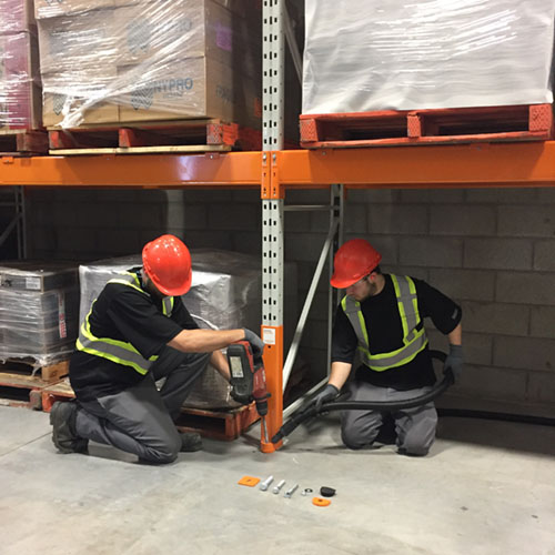A crew of rack installers in a warehouse